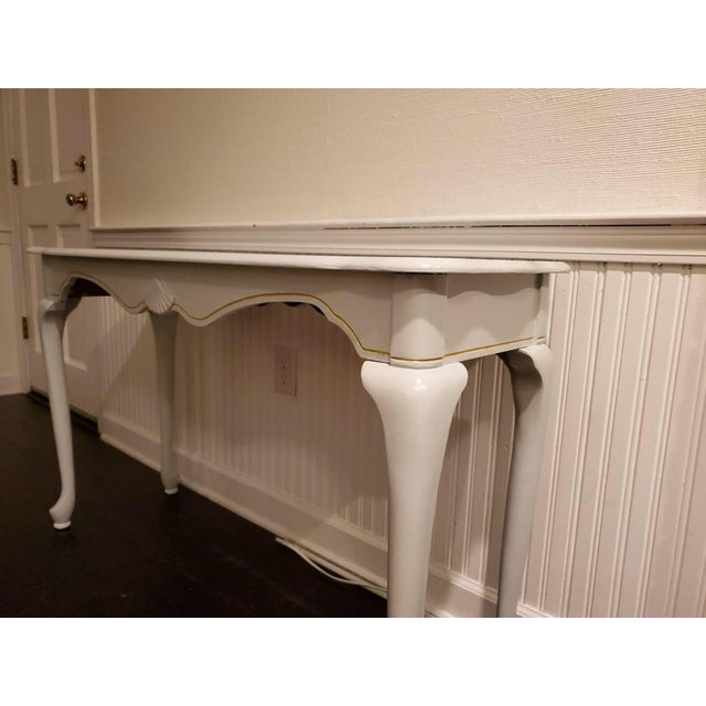 Beautifully restored French country console table. Light grey wash with gold accent