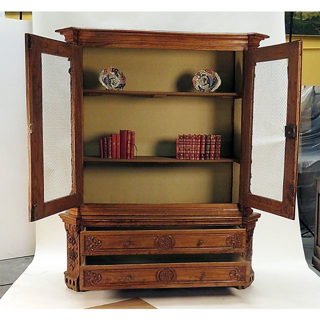A very richly carved cabinet in warm elm made in Northern Europe during the 18th or early 19th century. The carved...