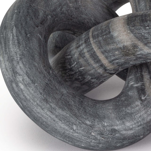 Hand-carved from a single piece of black stone, this abstract sculpture weaves about creating a flowing singular form. Add...