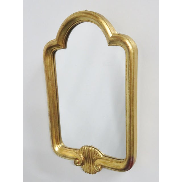 Diminutive Arched top gold gilt mirror with shell carved accent. Made in Italy