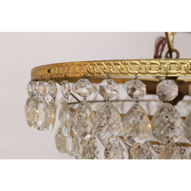 Gilt brass and crystal chandelier by Palwa in Germany. This mid-century modern - almost Hollywood Regency - chandelier can...
