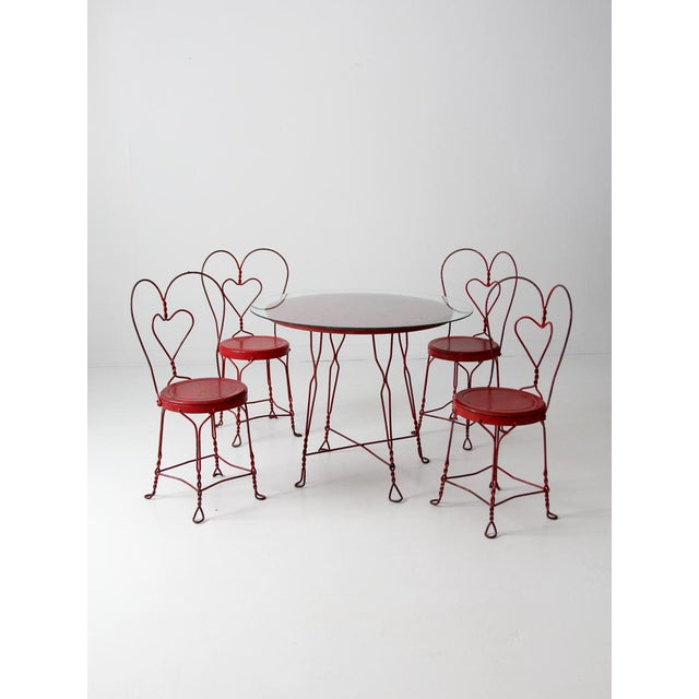 This is an art nouveau ice cream parlor table and chairs set from the early 20th century. The sweet red wrought iron...