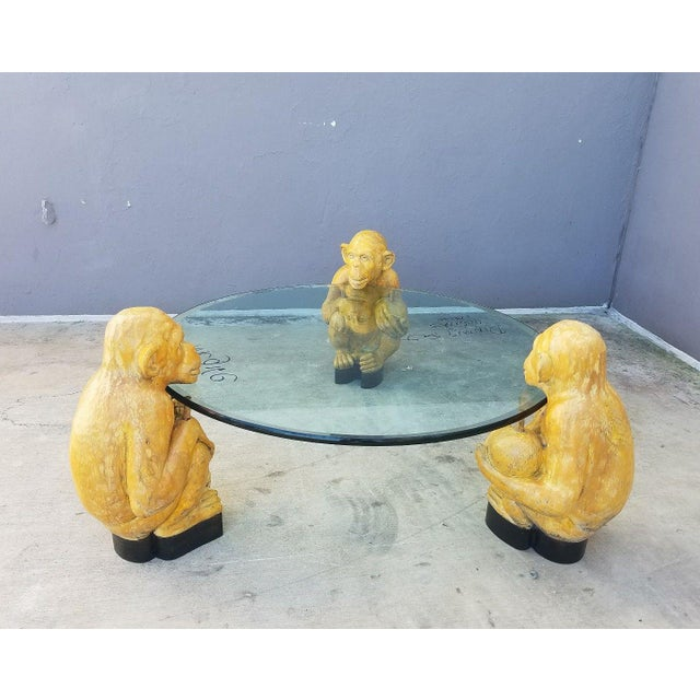 This is a 1970s vintage Italian glass coffee table. The piece features 3 hand carved monkey models that hold the glass top...