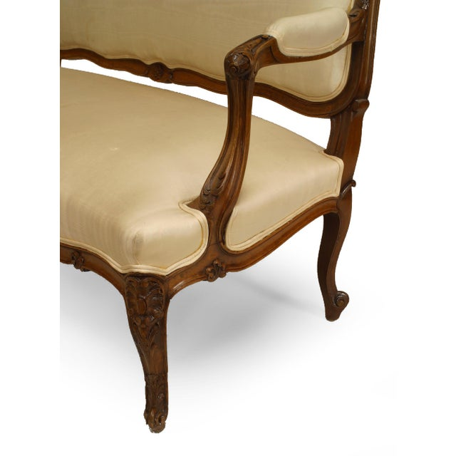 French Louis XV style (19/20th Cent) walnut settee with white upholstery and carved back crest