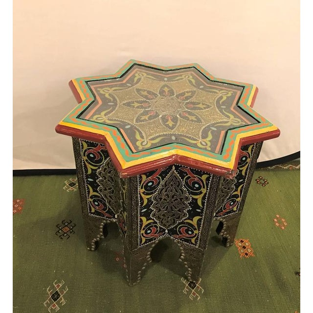 A star-shaped end table ebony inlays.The star-shaped wooden and brass table is featuring a dazzling swirl of images,...