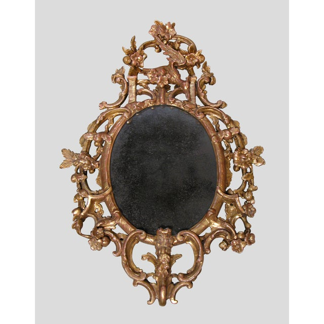 A well-carved English George II giltwood oval-form mirror surmounted by a bold crest of a hoho bird surrounded by a lively...