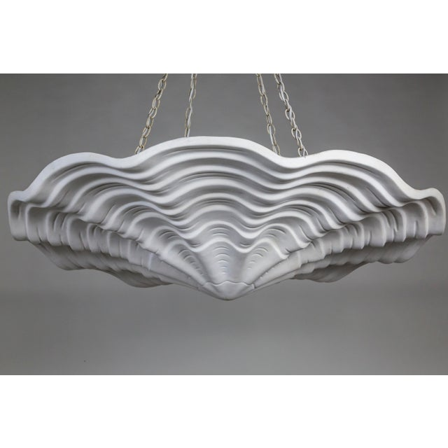 A lacquered plaster pendant in an undulating shell shape, with scalloped edges and imprinted lines accentuating the form....