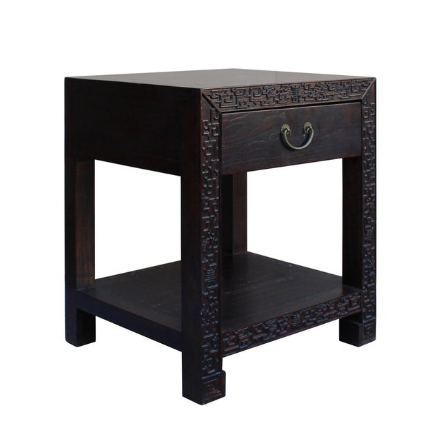 This is a simple oriental hardware accent end table / nightstand in brown color stain with natural wood pattern. There is...