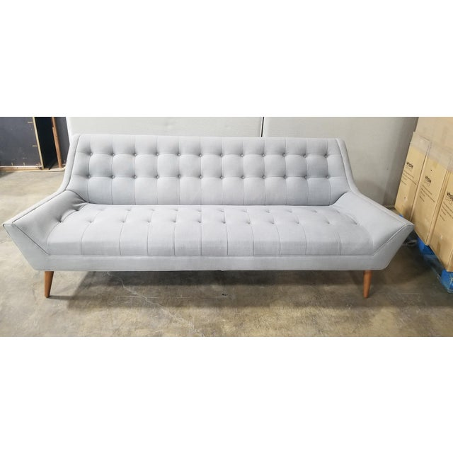 A gorgeous, new sofa designed in mid century style. With key design elements; tufted seat and back cushions and wood peg...