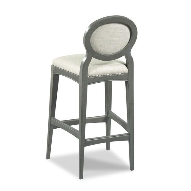 A sleek design with graceful tapered legs that are joined by low stretchers and curved apron rails. The stool features an...