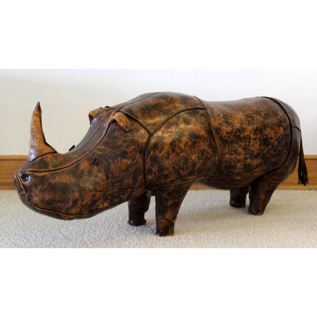 For your consideration is a stuffed, hand-stitched leather footstool, in the whimsical shape of a rhino, from a 1960s...