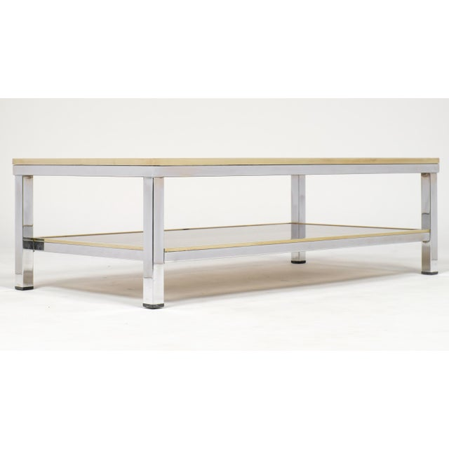 A mid-century modern chrome metal and brass coffee table with two smoked glass shelves attributed to Romeo Rega. The brass...