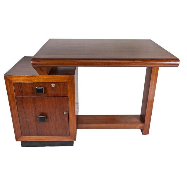 A teak wood asymmetrical desk with ebonized base and drawer pulls. Left side top drawer and cabinet below. Locks and keys...