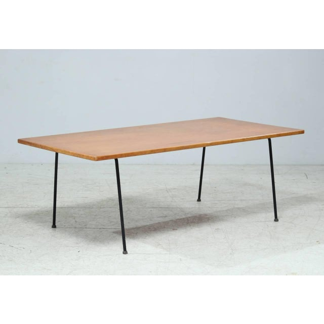 A rare coffee table by American designer Arden Riddle. The table is made of a thin wooden top, resting on a black, tubular...