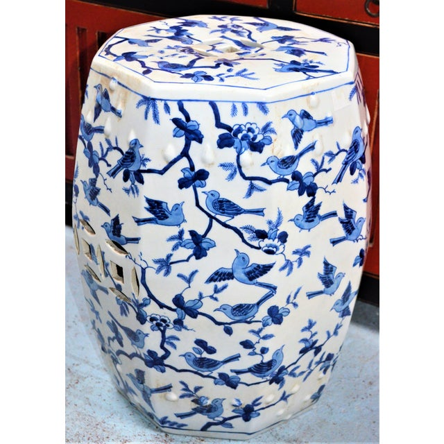 This is a beautiful blue and white porcelain garden stool with a vibrant design or small swallow birds flying arround and...