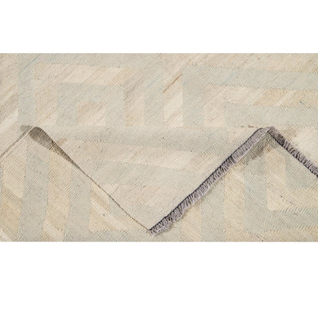 Stunning hand-knotted wool, contemporary Turkish Kilim rug. This rug has a beige field with an all-over geometric design...