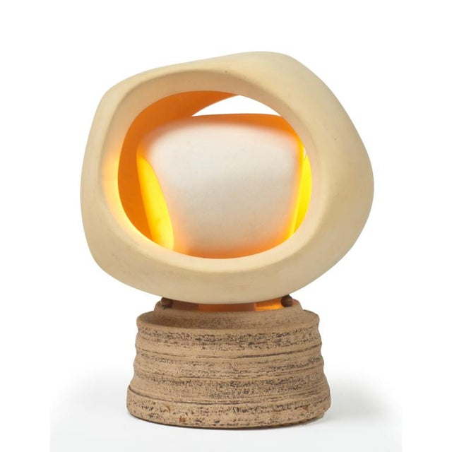 A nightlight with a pivoting inner and outer sculpted bisque shade assembly resting on a round stoneware base. By...