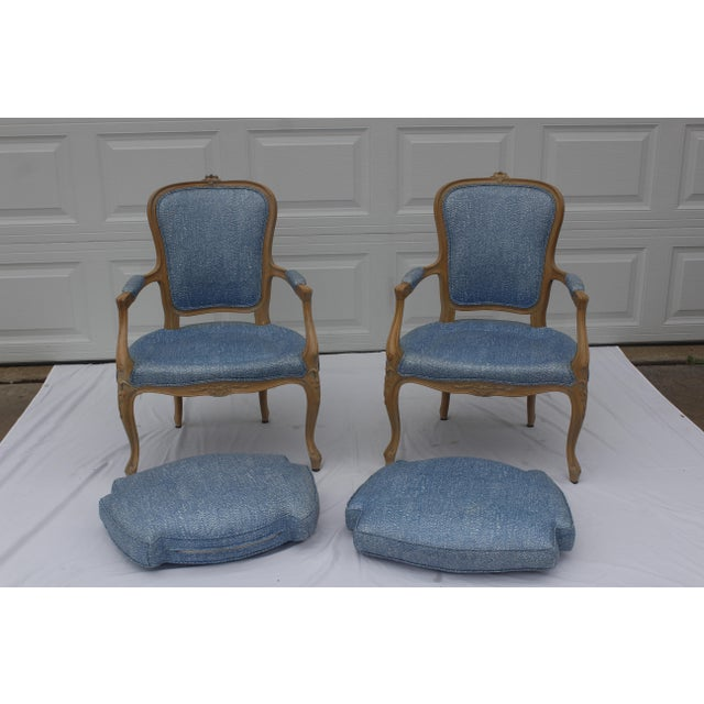 A pair of French Louis XVI style bergere armchair with stuffed down cushions. Beautiful blonde glazed wood with light blue...