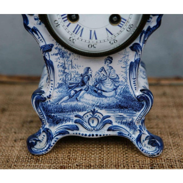 Decorated with figures, flowers, and seascapes in a deep blue, this baroque style, key wound, footed shelf clock has a...