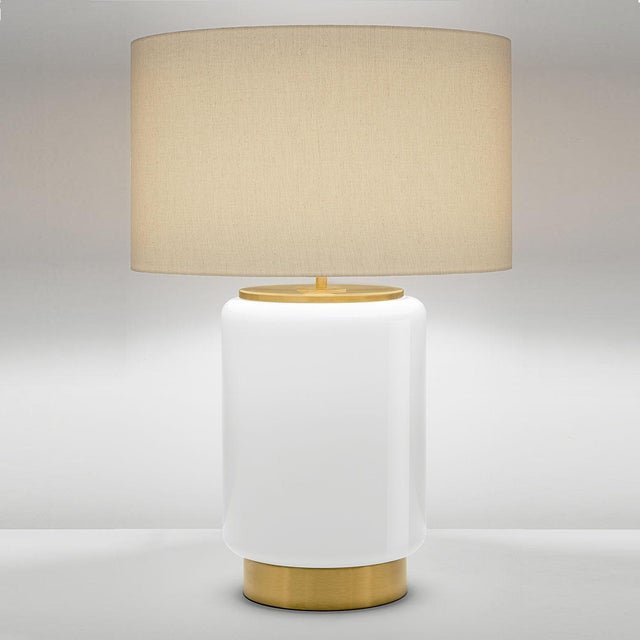 A mouthblown and scultured milk coloured glass lamp with shade on a brushed brass base and caps. Black silk covered cable....