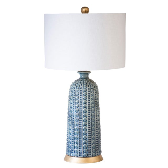 A shapely lamp, sure to turn heads. Tapered ceramic urn, in a beautiful blue or white glaze, sits on top of a simple metal...
