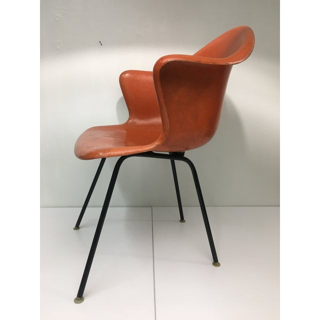 Consisting of burnt orange fiberglass shell and black steel base, this chair is very stable and structurally sturdy....