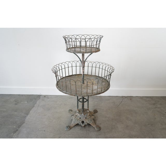 What you're seeing here is an antique Two-Tiered Planter made from iron with a sturdy base and arched wire surrounding the...
