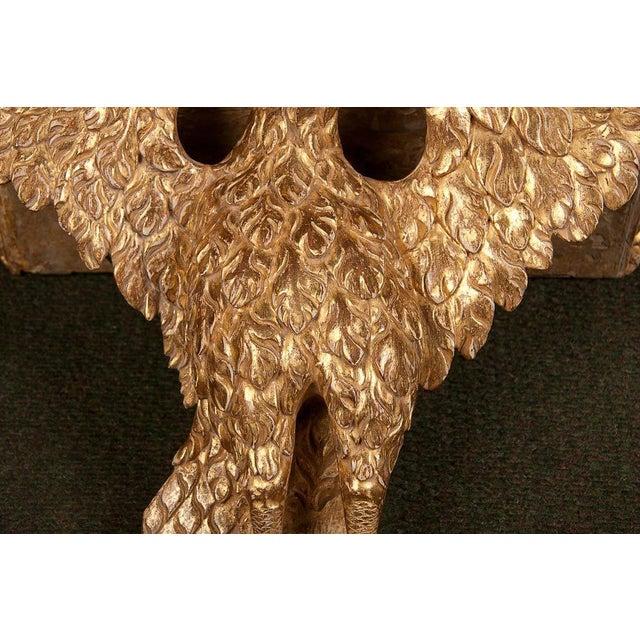 An English carved and gilt eagle form wall bracket. Re-gilt.