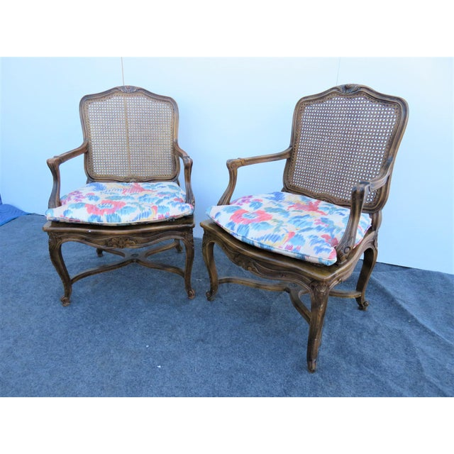 Louis XV style open arm chairs, oak frames with carved accents, x style stretchers, caned seat and backs, loose seat cushion