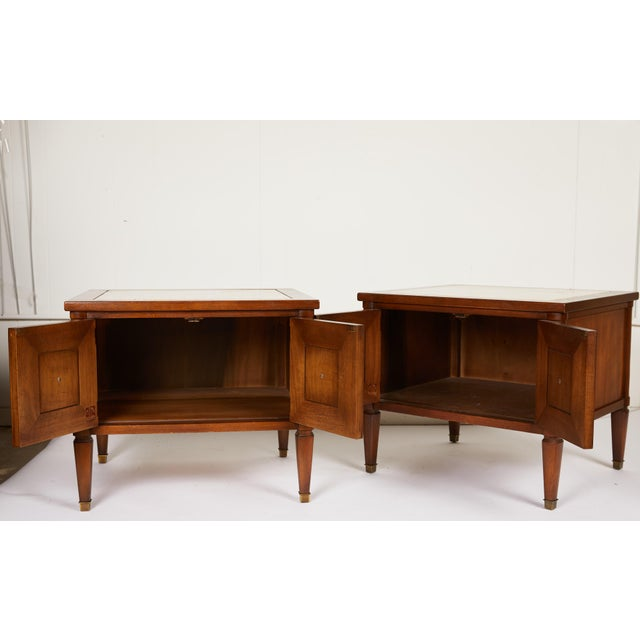 This Midcentury Italian pair of neoclassical style two-door end tables or bedside tables are made of walnut and finished...