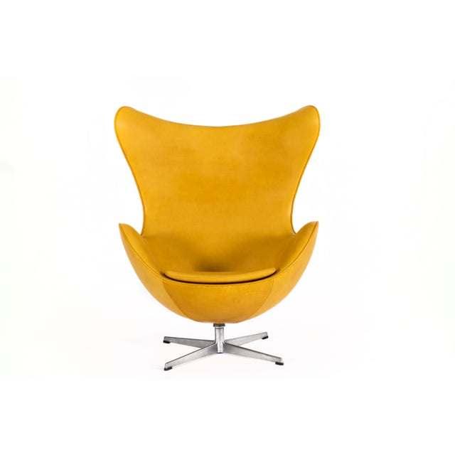 Jacobsen for Fritz Hansen pair of egg chairs and ottoman, reupholstered with vegetable dye leather. Ottoman measures: 22 W...