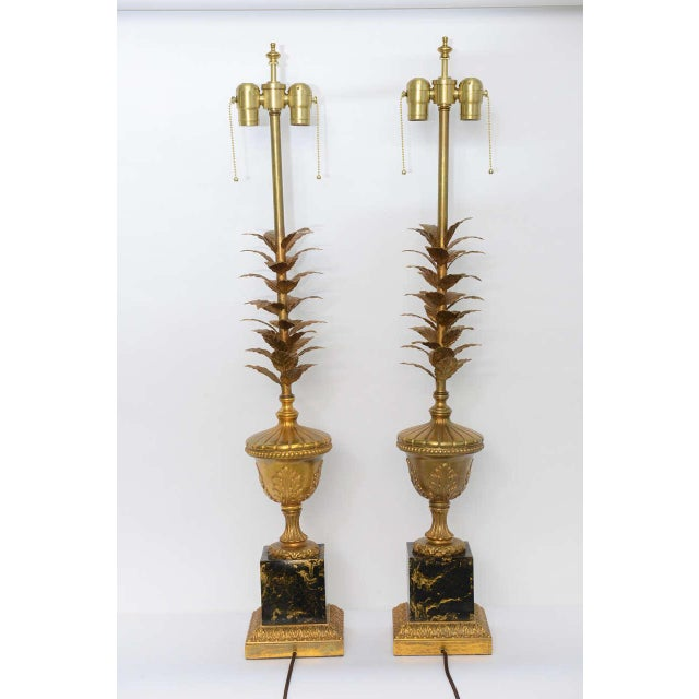REDUCED FROM $2,500. Featuring a double socket cluster, this pair of very elegant table lamps have a stem of gilt tole...