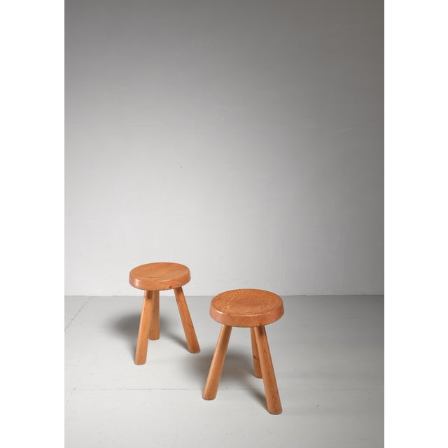 A pair of tripod pine stools by Charlotte Perriand, with a round seating (31 cm diameter). One of the stools has some user...