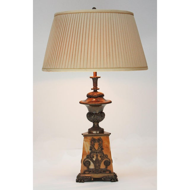 A handsome lamp with triangular gold marble base with gilt bronze decoration including feet, a bronze urn form tops the...