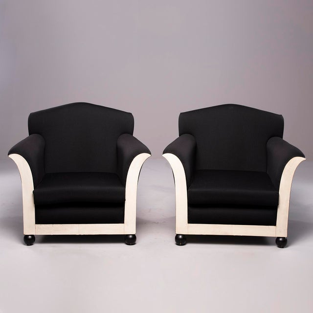 Circa 1930s pair of French club chairs with black upholstery. Front of chairs feature ball feet and flared arms with...