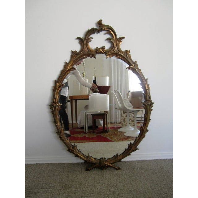 A beautiful and substantial vintage oval Italian gol giltwood carved wall mirror with a vine design . Marked 'Made in...