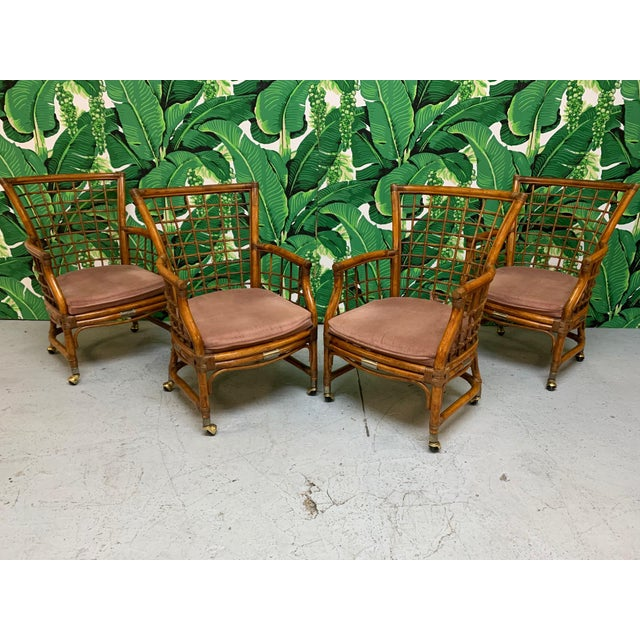 Mid Century rattan dining set features a rich, deep brown finish, brass accents, and a round glass top table. Chairs roll...