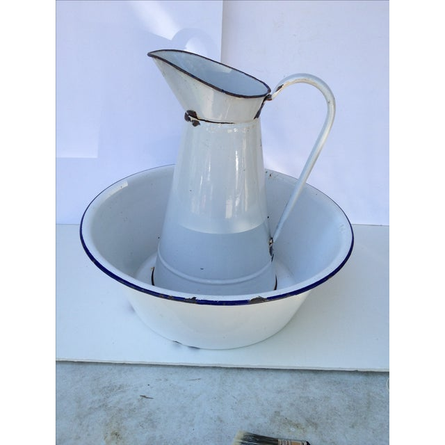 Very collectable, large French enamel pitcher and bowl set in white porcelain. This piece features chips, dings, and...