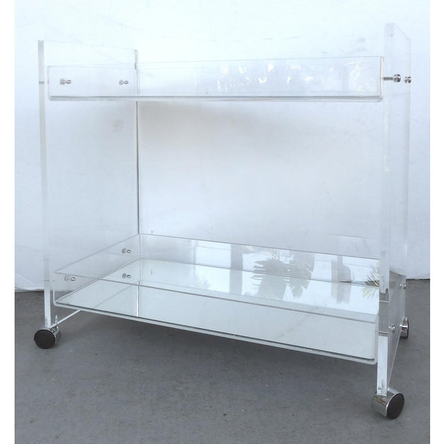 Offered for sale is a Lucite bi-level bar cart with mirrored shelf surfaces. The cart or trolley rolls on casters and can...