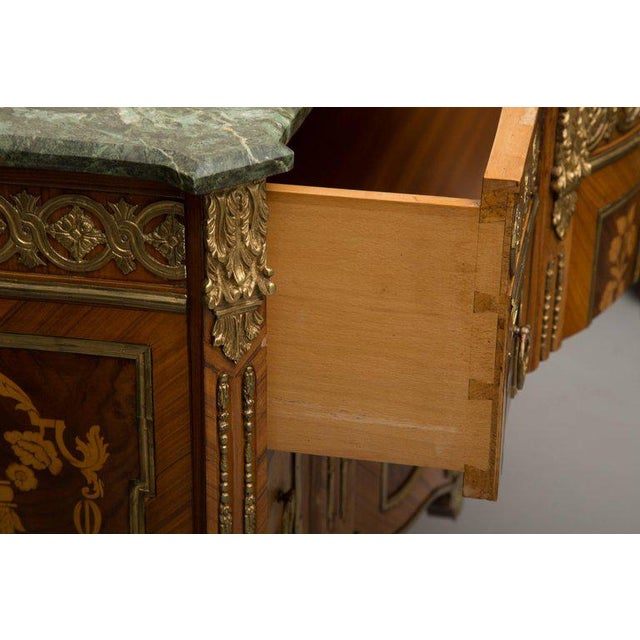 This is an imposing Louis XVI transitional style, the marble top with breakfront form over a gilt metal clad frieze above...