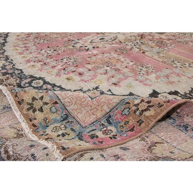 "A hand-knotted vintage Mashad rug with a medallion floral design on a red, ink blue field. This rug measures 10'4"" x 13'5""."