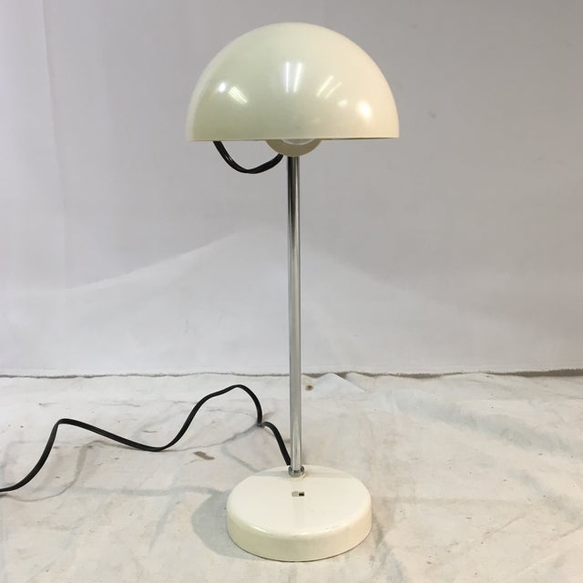 This vintage, minimalist white Lightolier desk lamp is emblematic of midcentury design. The bulb is cased in a shell-...