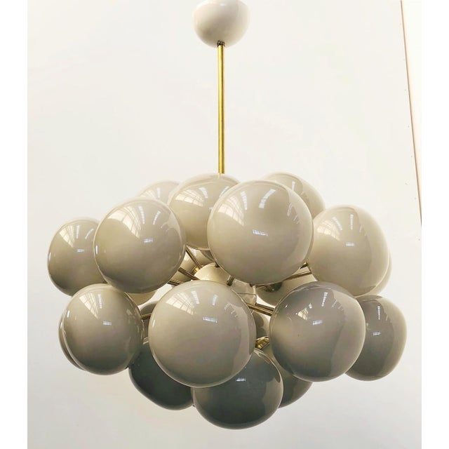 Italian oval shaped chandelier with dark gray Murano pebble shaped glasses mounted on natural brass frame, cream enameled...