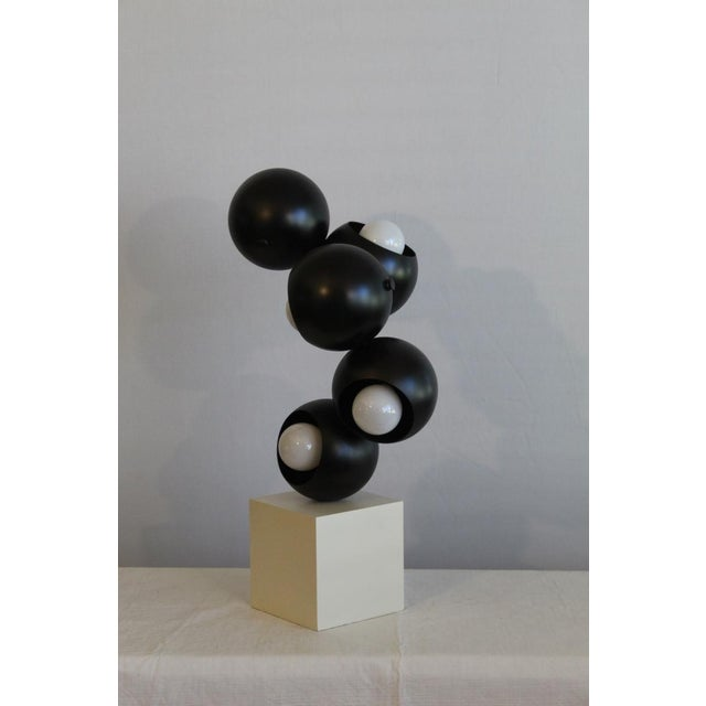 Beautiful sculptural table lamp. unique styling that Robert Sonneman is noted for. Black and white enameled finish that...