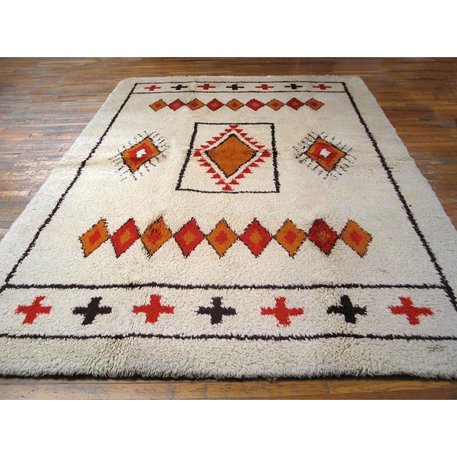 Offering a vintage Moroccan rug with an ivory background.