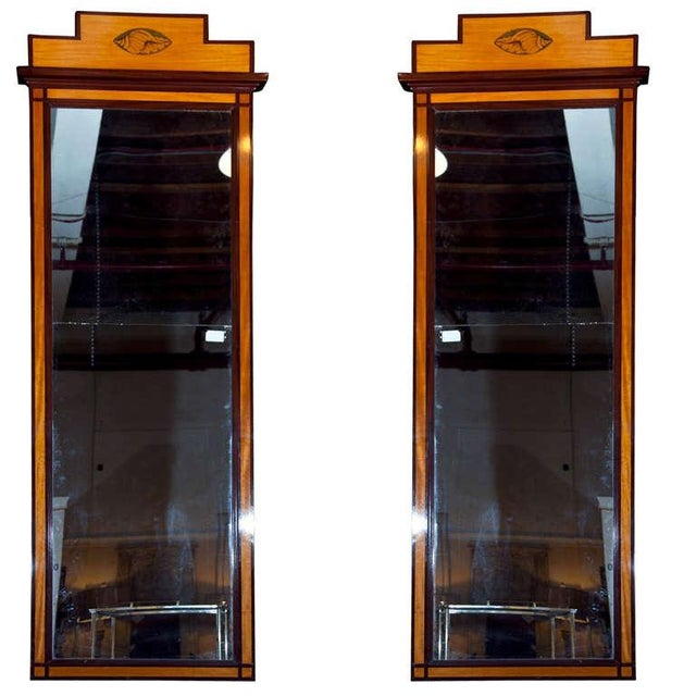 Monumental pair of Pier mirrors. Each satinwood frame having a mahogany trim banding leading to a top shell form inlaid...