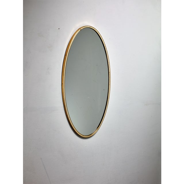 An oval shaped wall mirror with a double brass frame with a white inside rim. A simple and elegant design. A matching...