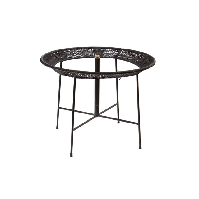 Round Iron and Raffia Dining Table with X base detail. This wrought iron table has an angled perimeter that is wrapped in...