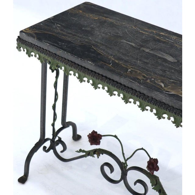 Wrought iron side table with thick black marble top. Decorated with forged metal roses.