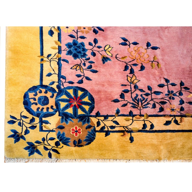 A gorgeous early 20th century Chinese Art Deco rug with a beautiful rose colored field surrounded by a soft champagne...